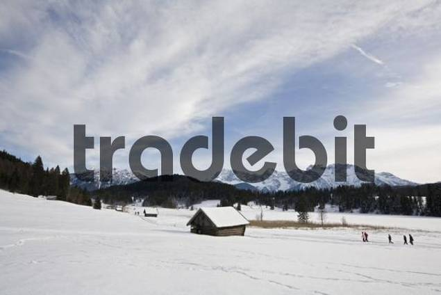 Hikers walking toward a cabin beside the Geroldsee Lake Gerold, Karwendel Range in the background, Bavarian pre-Alps, Upper Bavaria, Bavaria, Germany, Europe