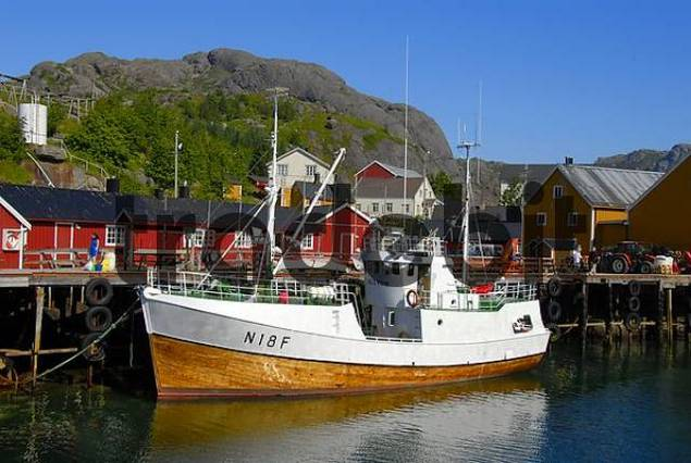 Wooden fishing boat tied up to a jetty and red wooden quotrorbuquot houses in Nusfjord, Lofoten Archipelago, Norway, Scandinavia