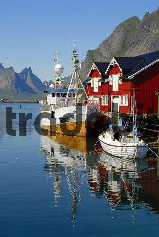View of boats in the harbour, red wooden quotrorbuquot houses, and mountains of Moskenesoya Island, Hamny, Reine, Lofoten Archipelago, Norway, Scandinavia