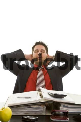 Young businessman sitting as his desk, leaned back in his chair, arms folded behind his head