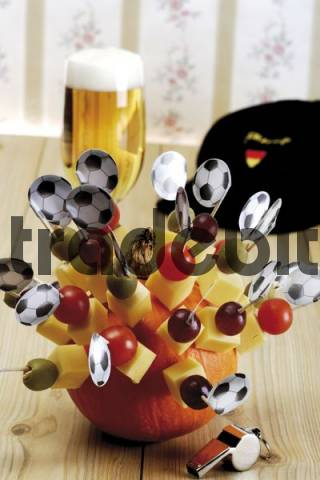 Cheese snacks, finger food, football flags, football memorabilia, ashtray, football cap, whistle and a glass of beer