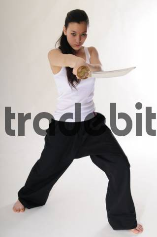 East Asian girl practicing Kung Fu with sword cutout