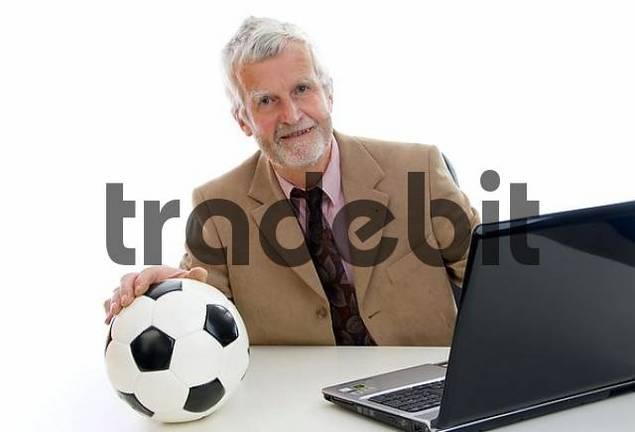 Older businessman working on laptop, football on his desk