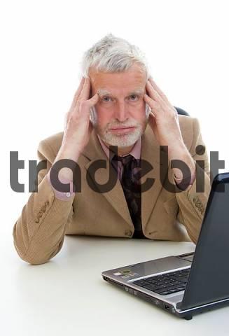 Older businessman working on laptop, overburdened