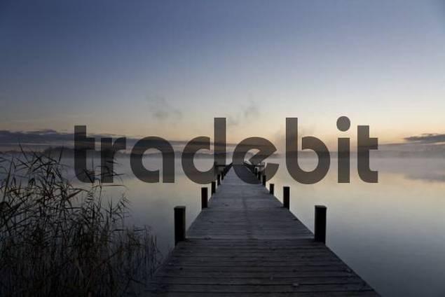 Mist over Lake Woerthsee at dawn, wooden dock, Bavaria, Germany, Europe