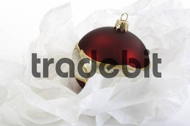 Red Christmas ornament and white tissue paper