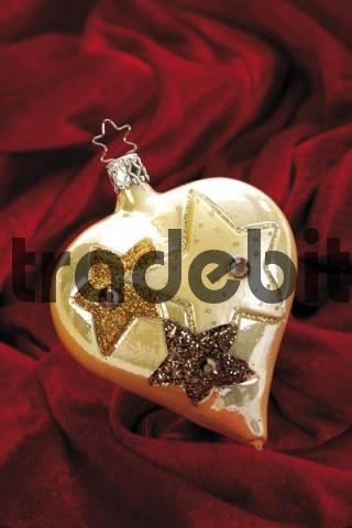 Gold heart-shaped Christmas ornament on red velvet
