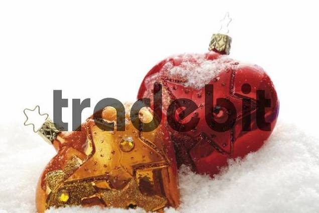 Copper-coloured and red heart-shaped Christmas ornaments on artificial snow