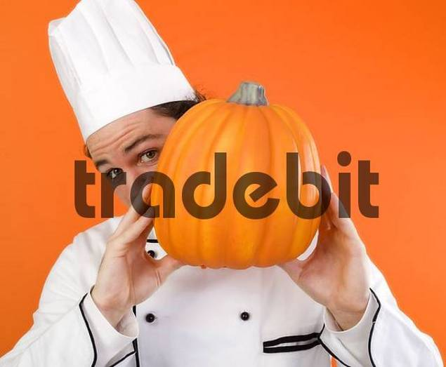Chef holding a pumpkin in front of his face