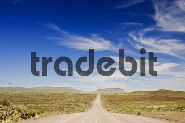 Long gravel road leading to arid rocky hills on the horizon in southern Namibia, Africa