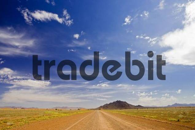 Gravel road leading to arid rocky hills at the edge of the Namib Desert, Namibia, Africa