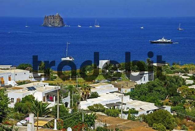 Yachts anchored around an unusual rock island, Stromboli, Southern Italy