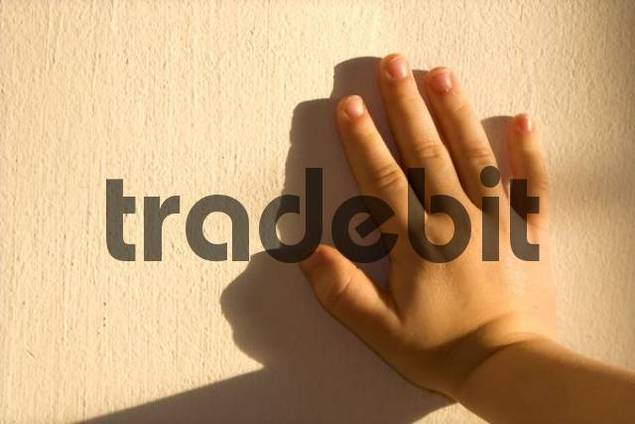 Childs hand pressed against a wall, shadow