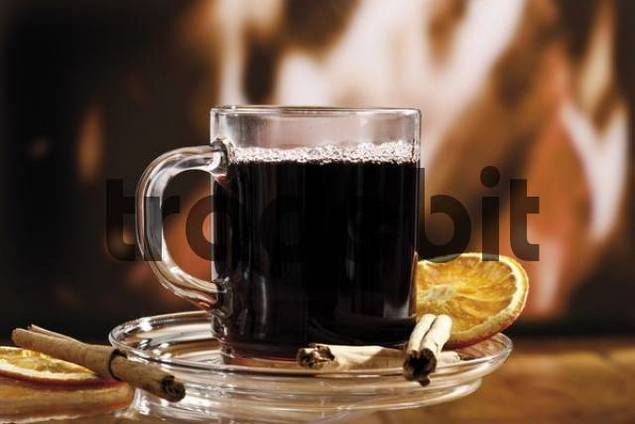 Glass of mulled wine garnished with cinnamon sticks and a dried orange slice in front of a fireplace