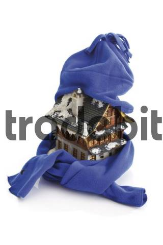 House wrapped in scarf and hat - symbol for saving energy, energy conservation