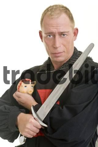 Darsteller eines Tempelritters bewacht mit einem Dolch bzw. einem Schwert ein Sparschwein