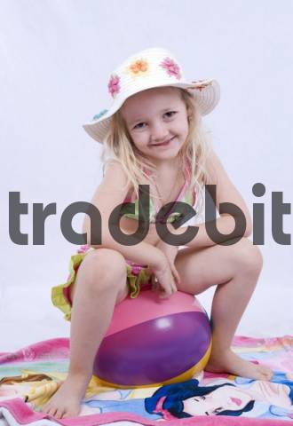 Young girl wearing bikini top and skirt sitting on a rubber ball