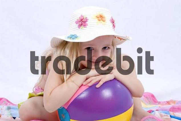 Young girl wearing summer clothes leaning on a rubber ball