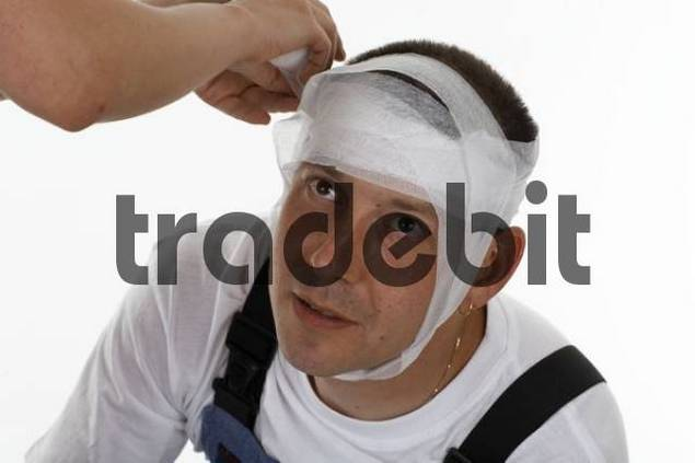 Mans head being bandaged, dressed