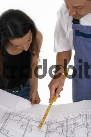Workman and a woman looking over blueprints, construction plans