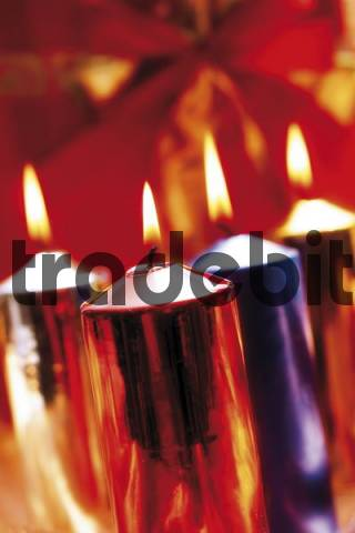 Burning candles, lit candles, different metallic colours