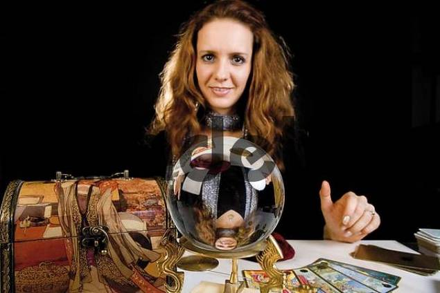 Fortune teller in front of a crystal ball with cards