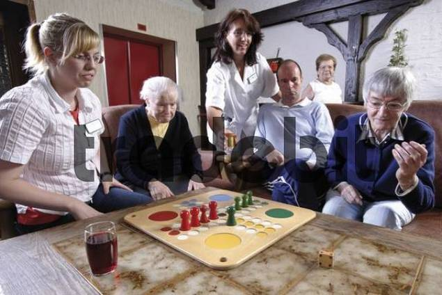 Nurses and residents of an old-age home or nursing home playing board games in the afternoon