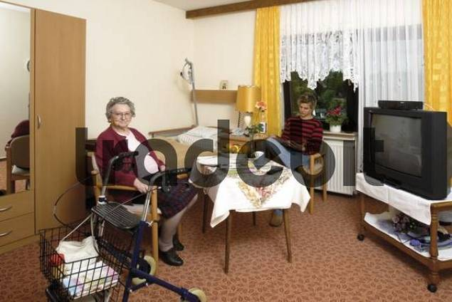 Elderly woman visited by her grandson at a nursing home