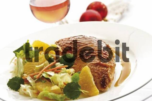 Roasted chicken breast on a plate with a salad containing orange segments beside Christmas decorations