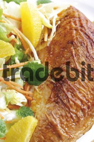 Roasted chicken breast served with a salad containing orange segments