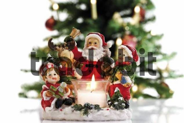 A tea light holder consisting of a Santa Claus, a reindeer and children as Christmas decoration