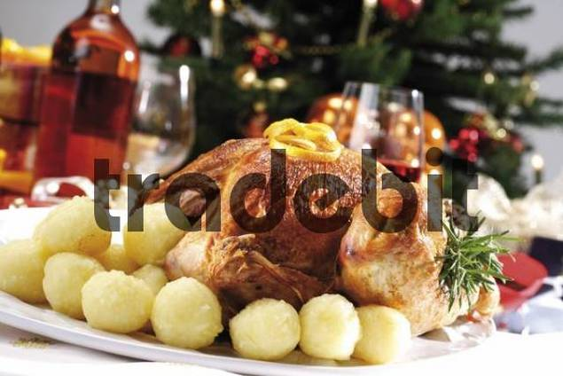 Roast turkey on a festive table setting served with dumplings in front of a decorated Christmas tree