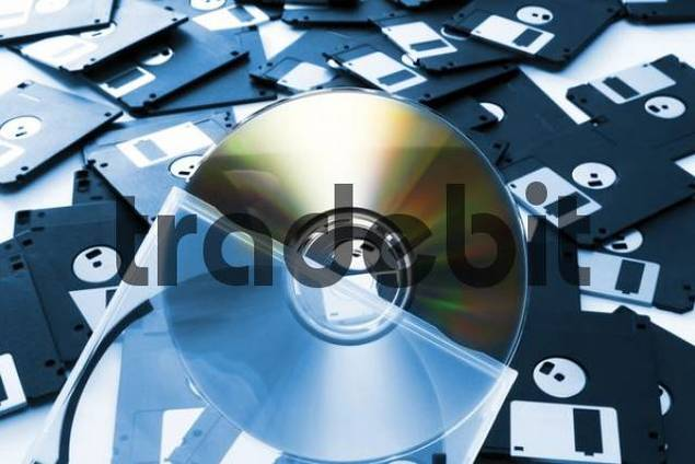 CD half out of its transparent holder in front of floppy disks