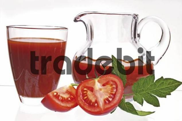 Tomato juice in a glass and jug, cut fresh tomato front