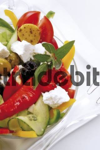 Greek salad in a glass bowl with feta cheese, gherkins, tomatoes, chilli peppers, and green and black olives