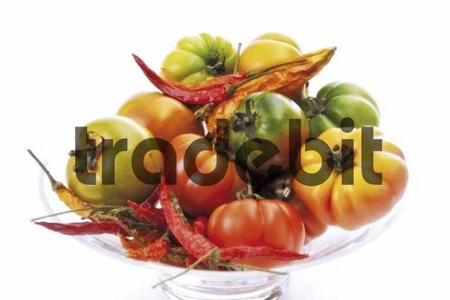 Assorted tomato types and red hot chili peppers in a glass bowl