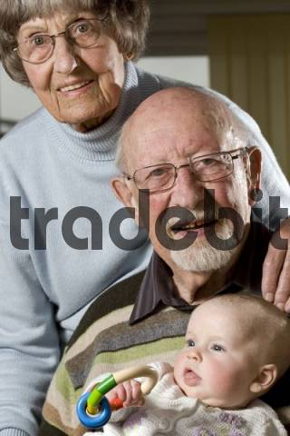 Happy retired couple, pensioners and their grandchild