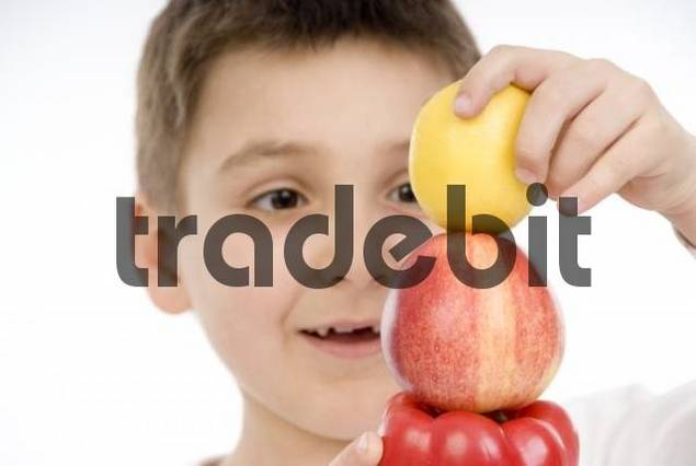 7-year-old boy stacking a pepper, an apple and a lemon