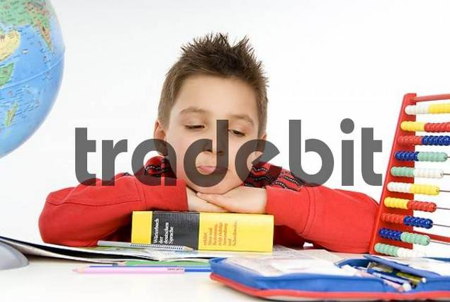 7 year-old schoolboy sitting at his desk, not concentrating