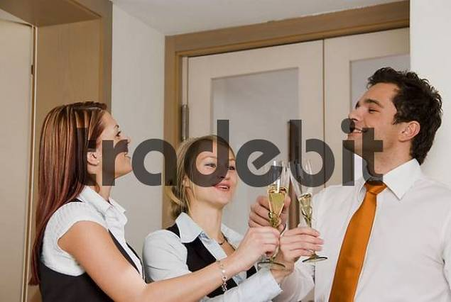 Three young businesspeople with sparkling wine glasses, toasting, clinking glasses