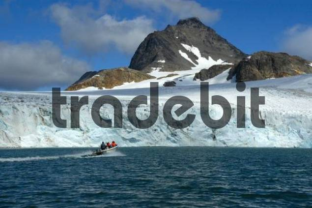 Small motorboat in front of a large ice wall or ice face, Apusiak Glacier and Mountains, eastern Greenland, Arctic