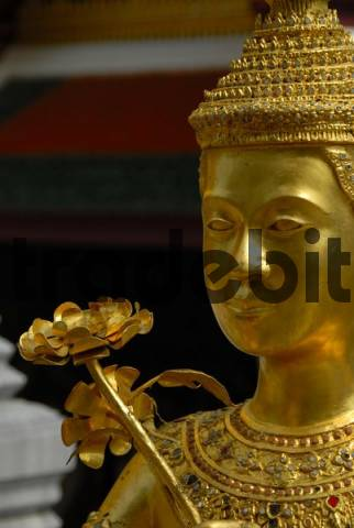Mythic golden statue with flower at the Grand Palace in Bangkok, Thailand, Southeast Asia