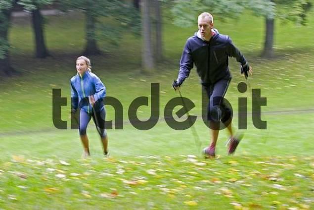 zwei nordic walker mit st cke und sportliche kleidung laufend. Black Bedroom Furniture Sets. Home Design Ideas