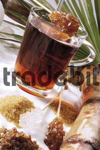 Tea in a glass surrounded by various kinds of sugar