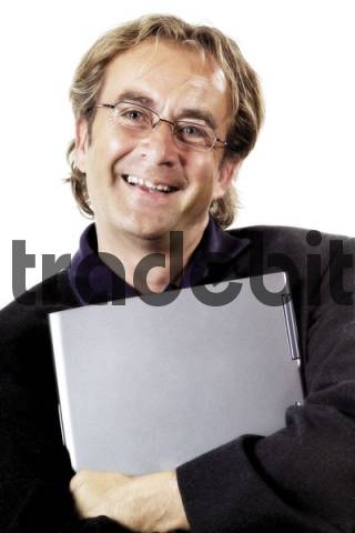 Smiling man wearing glasses holding a laptop under his arm
