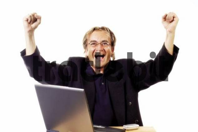 Man sitting in front of laptop celebrating, success