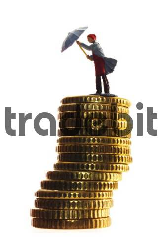Miniature woman standing on a stack of coins, opening an umbrella