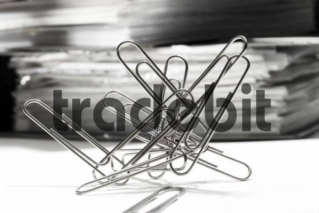 Paperclips, paper clips in front of a stack of files