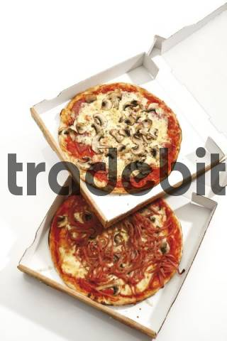 Prosciutto and mushroom pizzas in a delivery boxes