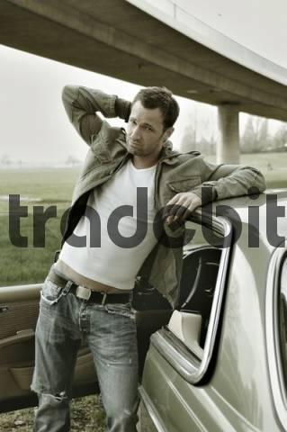 31-jähriger Mann als James Dean am Auto lehnend